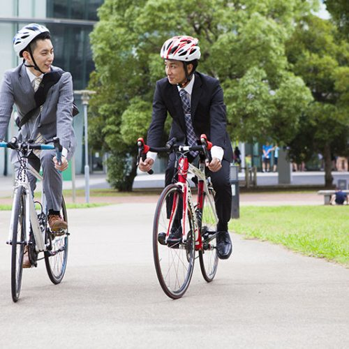 two men in business suits riding bicycles