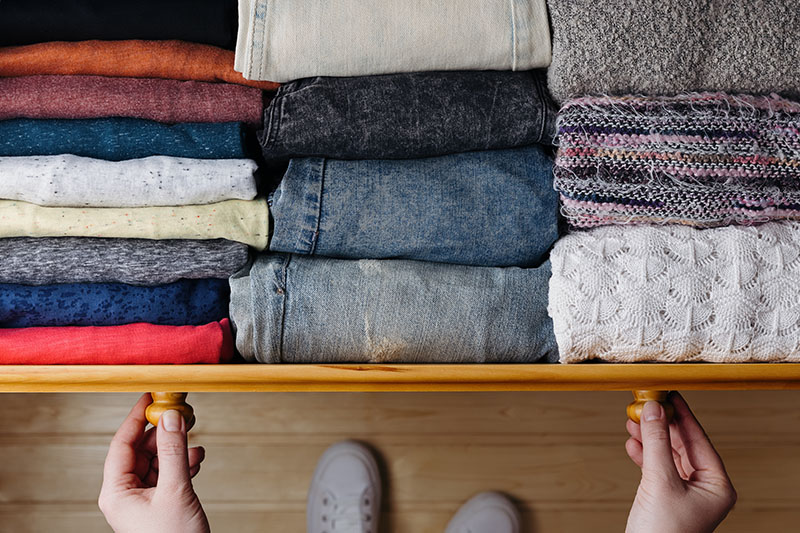 hands pulling open drawer of folded clothes