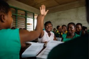 woman smiling and raising hand in classroom