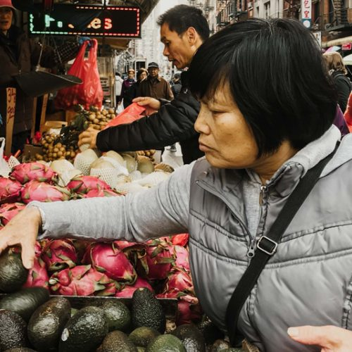 woman choosing produce at a market