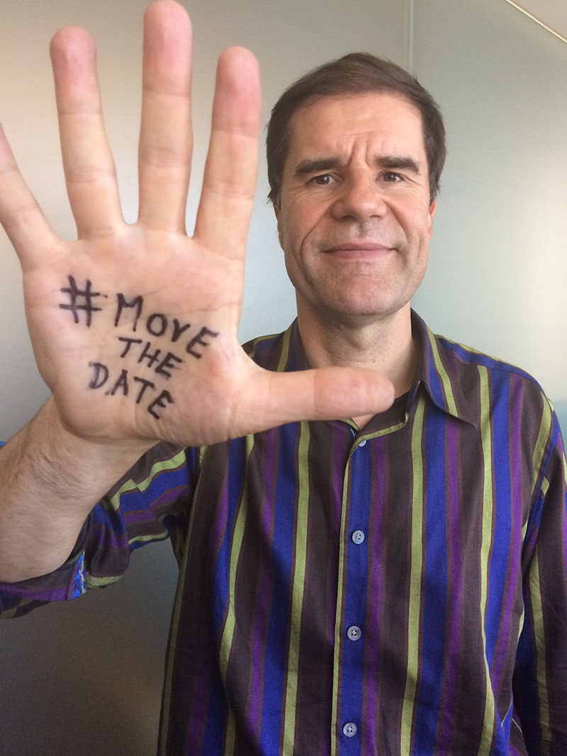 Man with #MoveTheDate text on palm
